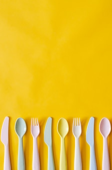 Colorful fork, spoon and knife on yellow background with empty space for text.