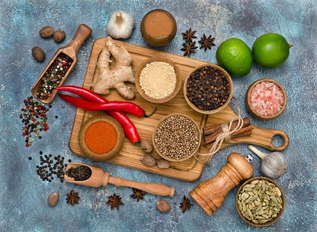 木製のキッチンボードとライムで調理するためのカラフルな香りのよいスパイス。上面図。フラットレイ。