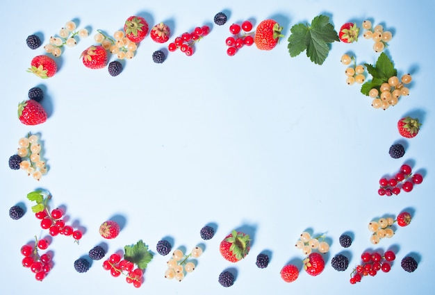 Colorful frame made with blackberry, strawberry, red and white currant on blue