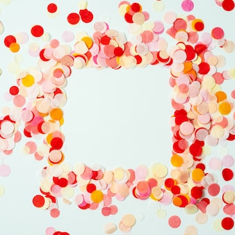 Colorful frame made with red and orange festive confetti on pastel background