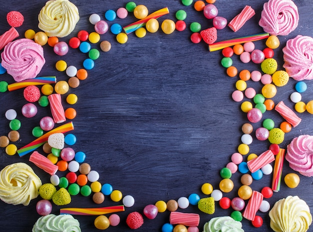Colorful frame of multicolored candies on black wooden background