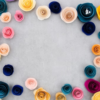 Colorful frame with paper flowers on cement background