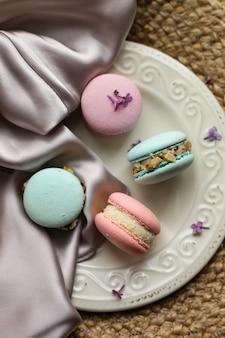 짚과 아틀라스 천 배경에 라일락 꽃과 함께 접시에 다채로운 프랑스 디저트 마카롱 또는 마카롱.