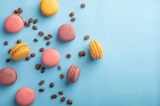 Colorful french or italian macaron stack and coffee bean on blue table