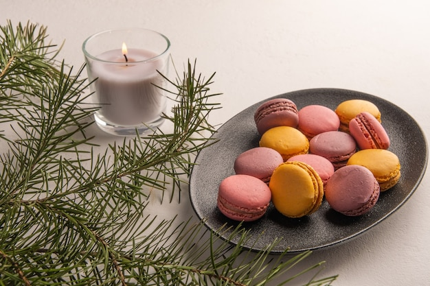 Colorful french or italian macaron stack on dark plate put on white table near fir branch and