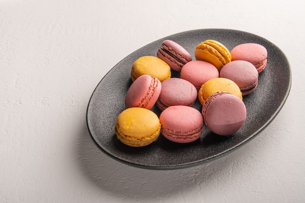 Colorful french or italian macaron stack on dark plate put on white table with for
