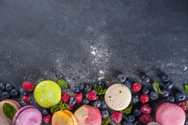カラフルなフレンチマカロンデザート。濃い灰色の石の背景にベリー、砂糖粉、ミントとさまざまな味と色のマカロンクッキーのセット