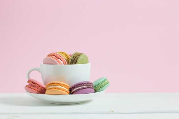 Colorful french macarons in cup on white wooden background.