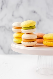 Colorful french macarons on a pink plate on marble