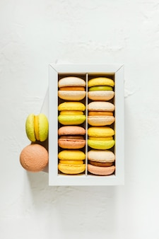 Colorful french macarons in a white box on white, top view