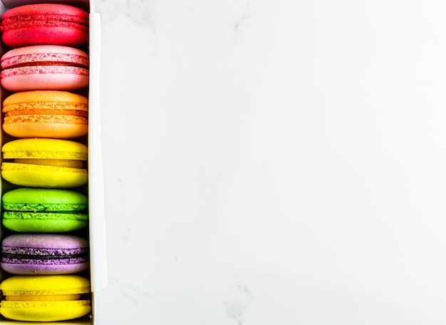 Colorful french macaroons in box on modern table background, top view