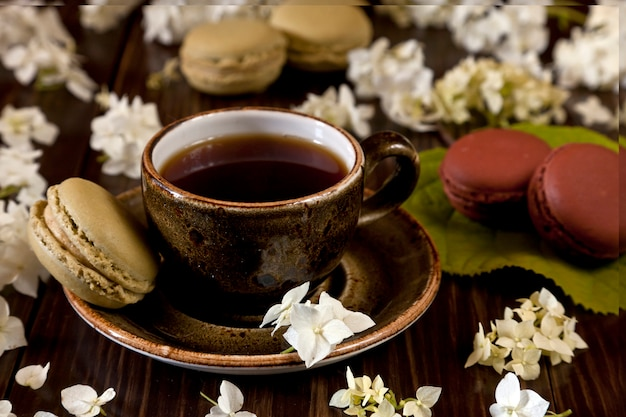 Colorful french macaroons,  and cup of coffee surrounded by  flowers of hortensia on rustic brown wooden. top view, close up