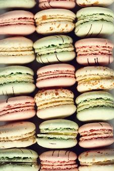 カラフルなフランスのマカロンは平らに置きます。休日やお祝いのコンセプトです。女性のための甘い贈り物、女の子