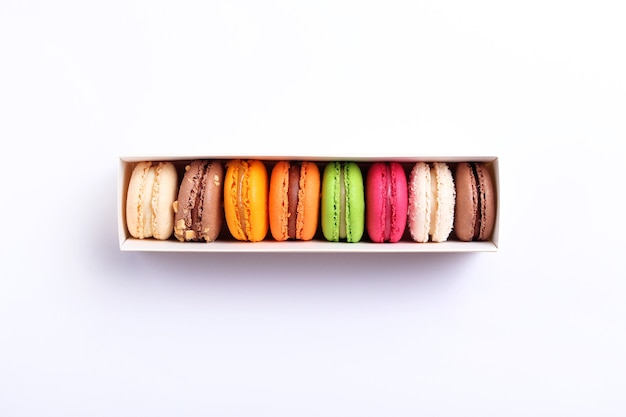 Красочные французские миндальное печенье в подарочной коробке на белом фоне. миндальное печенье. вид сверху, плоская. день святого валентина сладкий подарок концепция, праздник, праздник.