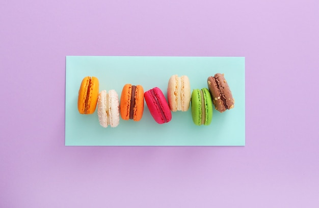Colorful french macaroons on mint and purple background