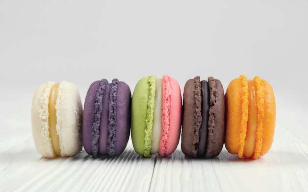Colorful french macaroons on white wooden table