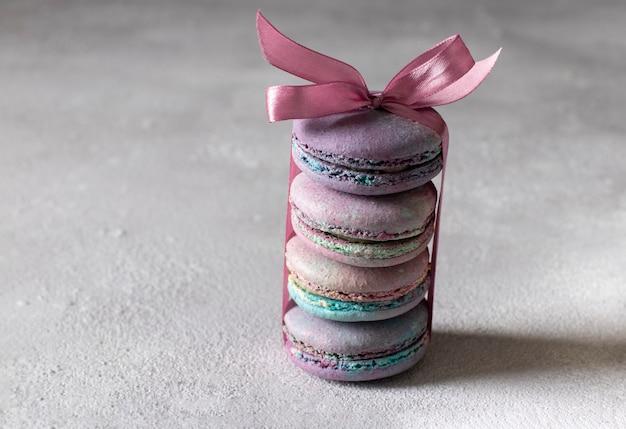 明るい灰色の背景にピンクのリボンで結ばれたdorブルーチーズとカラフルなフレンチマカロン。水平フォーマット