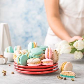 Красочные французские или итальянские макароны укладываются на красную тарелку. десерт к послеобеденному чаю или кофе-брейку. фон красивая еда с рукой женщина