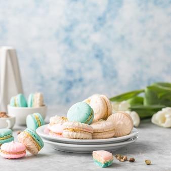 흰색 접시에 다채로운 프랑스어 또는 이탈리아어 macarons 스택. 애프터눈 티 또는 커피 브레이크와 함께 제공되는 디저트. 아름다운 식사 배경