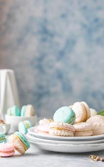 カラフルなフランスまたはイタリアのマカロンが白いプレートに積み重ねられています。アフタヌーンティーやコーヒーブレイクを添えたデザート。美しい食事の背景
