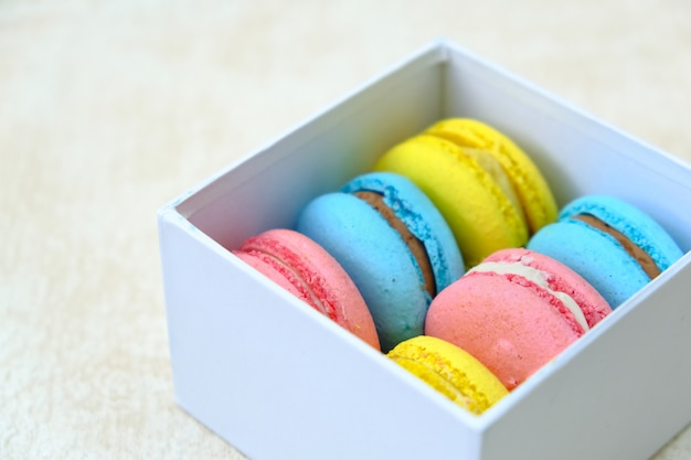 白いギフトボックスにカラフルなフランスの甘いケーキマカロン。カフェやベーカリーの広告用。