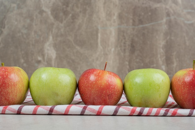 Красочные свежие яблоки на полосатой скатерти.