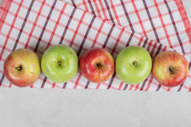 Colorful fresh apples on striped tablecloth