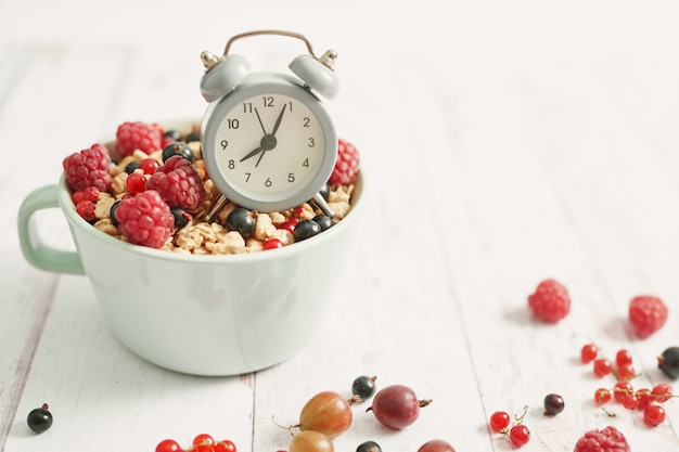 Colorful fresh berries with flakes in a white cup and alarm clockt