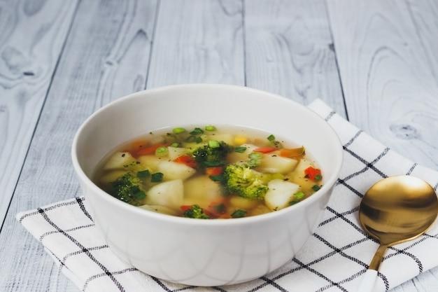 木製の灰色の背景にキッチン クロスのボウルにカラフルな新鮮な春のスープ