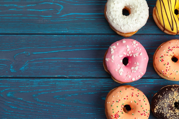 Colorful fresh donuts on dark blue wooden background