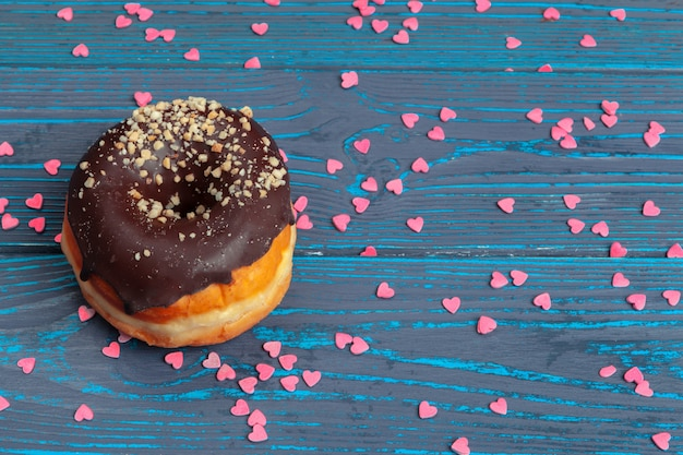 Colorful fresh donuts on dark blue wooden surface