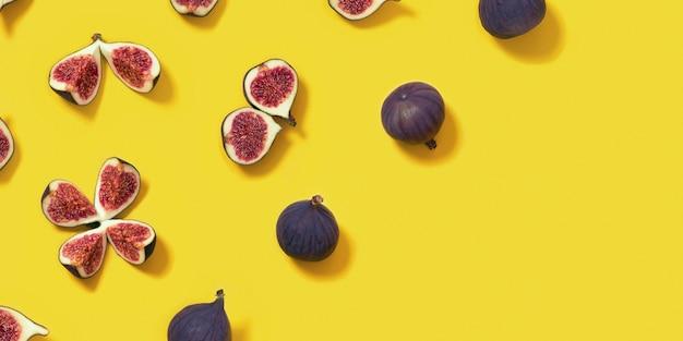 明るい黄色の背景、全体とスライスしたイチジクのカラフルな新鮮なイチジクの果実のパターン。上面図、フラットレイ、コピースペース。