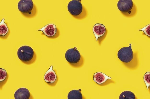 明るい黄色の背景全体とスライスしたイチジクのカラフルな新鮮なイチジクのフルーツパターン