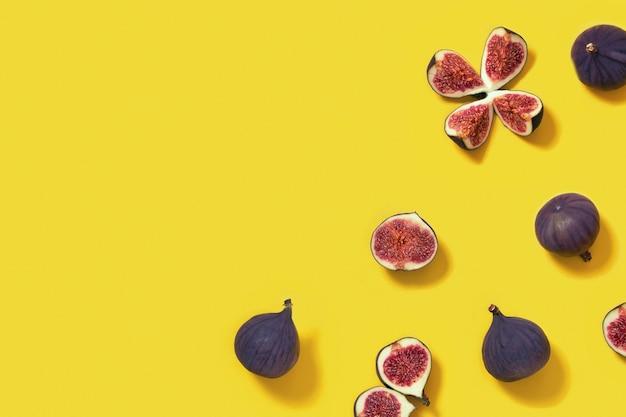 明るい黄色の背景、全体とスライスしたイチジクのカラフルな新鮮なイチジクのフルーツパターン。