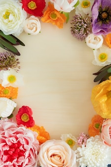 Colorful fresh flowers frame on beige background