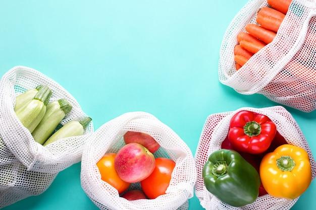 파란색 배경에 재사용 가능한 면 가방에 다채로운 신선한 과일과 야채. 제로 폐기물 또는 책임 있는 식품 쇼핑 및 보관 개념. 지속 가능한 라이프 스타일 프레임 배경
