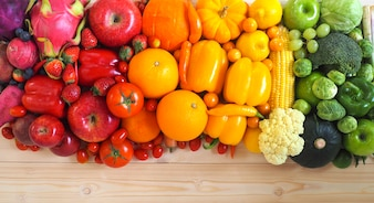 Colorful fresh fruits and vegetables on wood background.