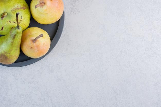 黒のプレートにカラフルな新鮮な梨。