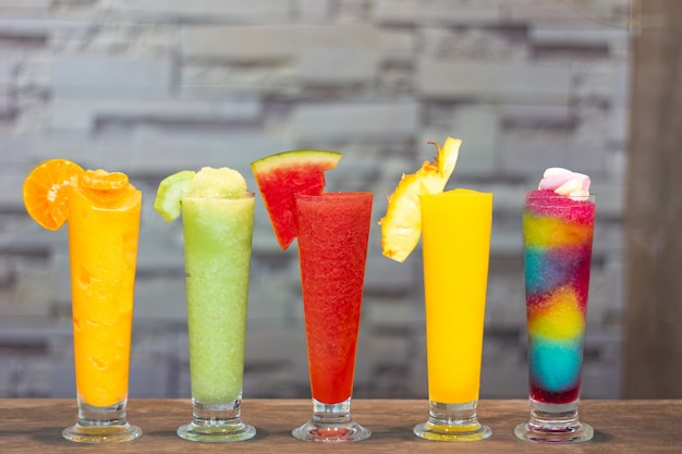 Colorful fresh smoothies with tropical fruits on grey background