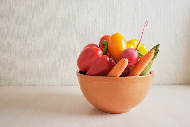 Colorful fresh vegetable in bowl and on wooden table copy space