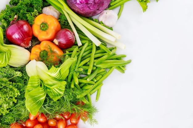 白い背景の上の食事療法のためのカラフルな新鮮な野菜。