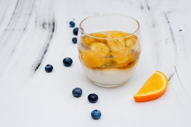 블루베리와 흰색 배경에 유리에 다채로운 과일 젤리.