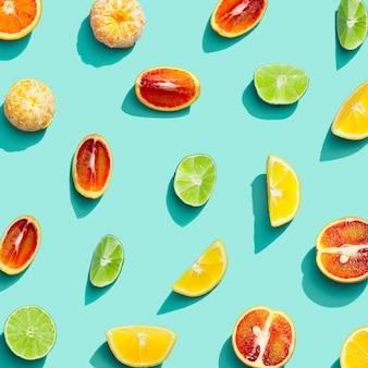 青い背景に新鮮な柑橘類、レモン、赤オレンジ、タンジェリン、ライムからカラフルなフルーツパターン