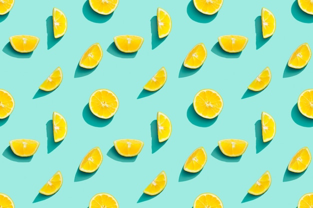 Colorful fruit pattern from fresh citrus yellow lemon on blue background summer food