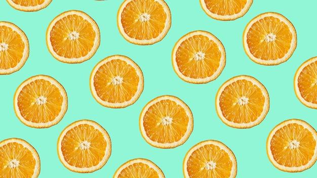현대적인 파란색 배경에 신선한 오렌지 조각의 다채로운 과일 패턴입니다. 평면도에서
