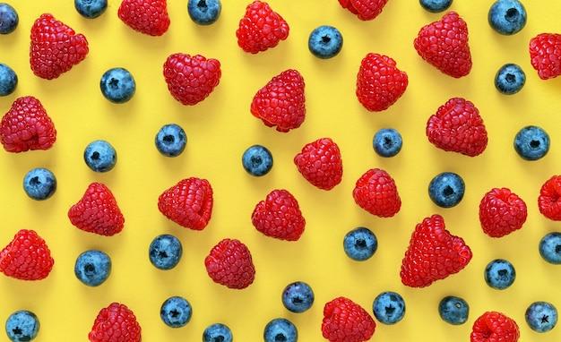 Красочный фруктовый образец малины и черники на желтом фоне. плоская планировка. вид сверху