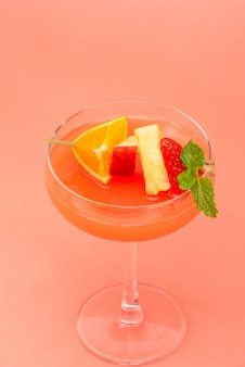 Colorful fruit punch cocktail drink in coupe glass