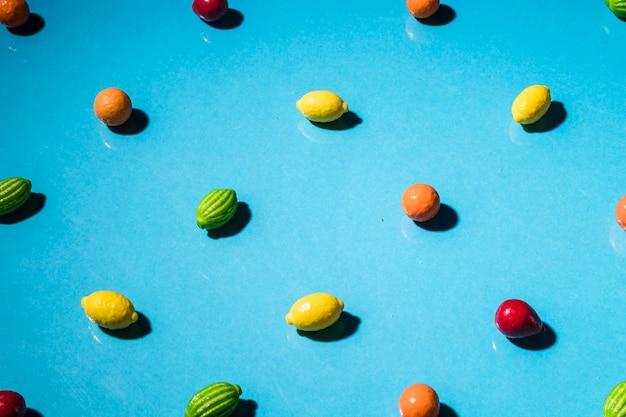 Colorful fruit shape candies on blue wallpaper