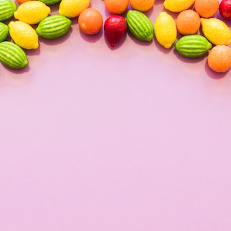 Colorful fruit shape candies forming top bottom over the pink backdrop