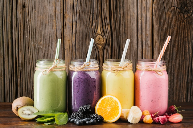 Colorful fruit and smoothies composition on wooden background